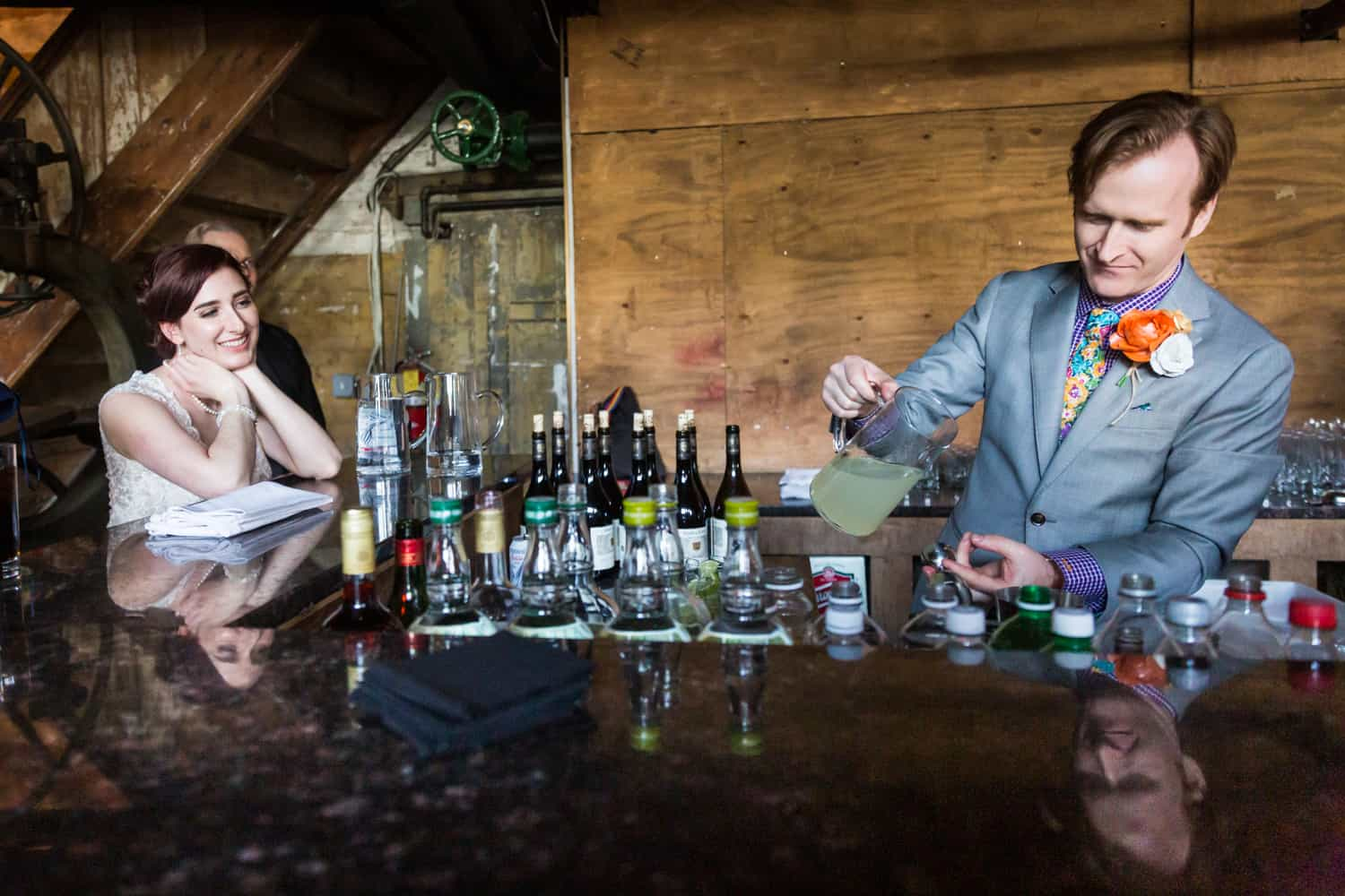 Groom preparing cocktail for bride at a Greenpoint Loft wedding