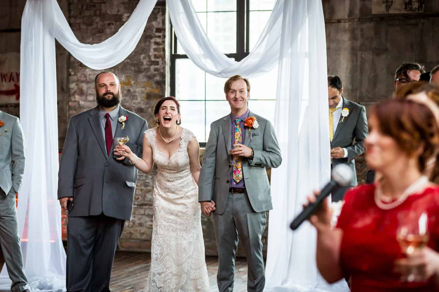 Bride and groom laughing at speeches at a Greenpoint Loft wedding