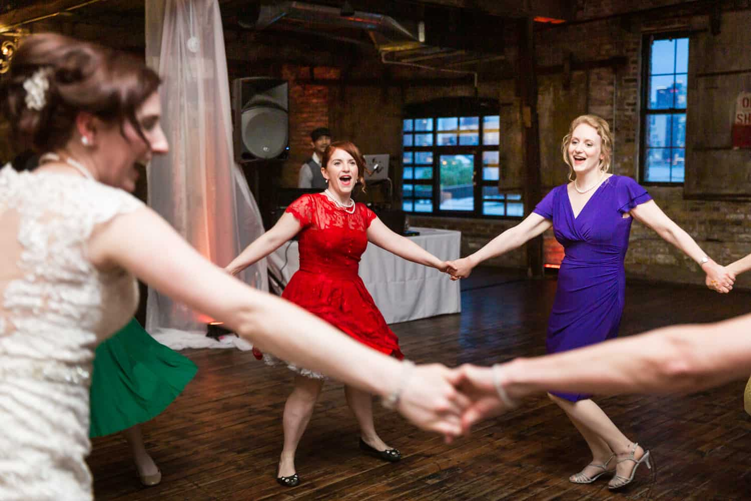 Bride and bridesmaids dancing in circle at a Greenpoint Loft wedding