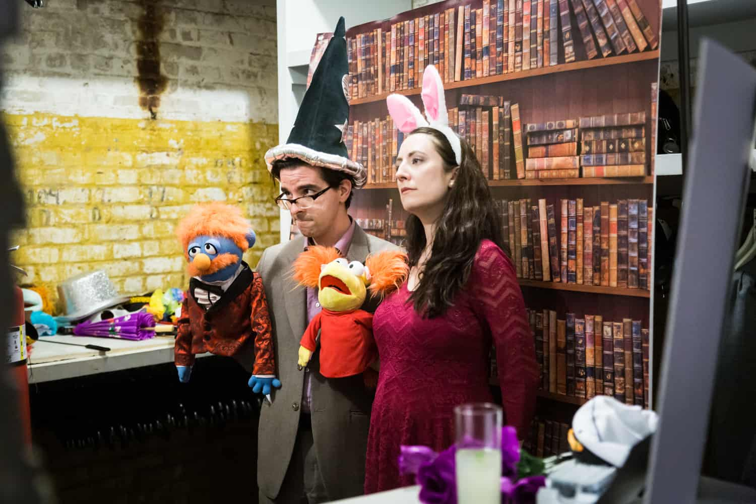 Couple dressed in bunny ears and wizard hat and holding puppets at a DIY photo booth