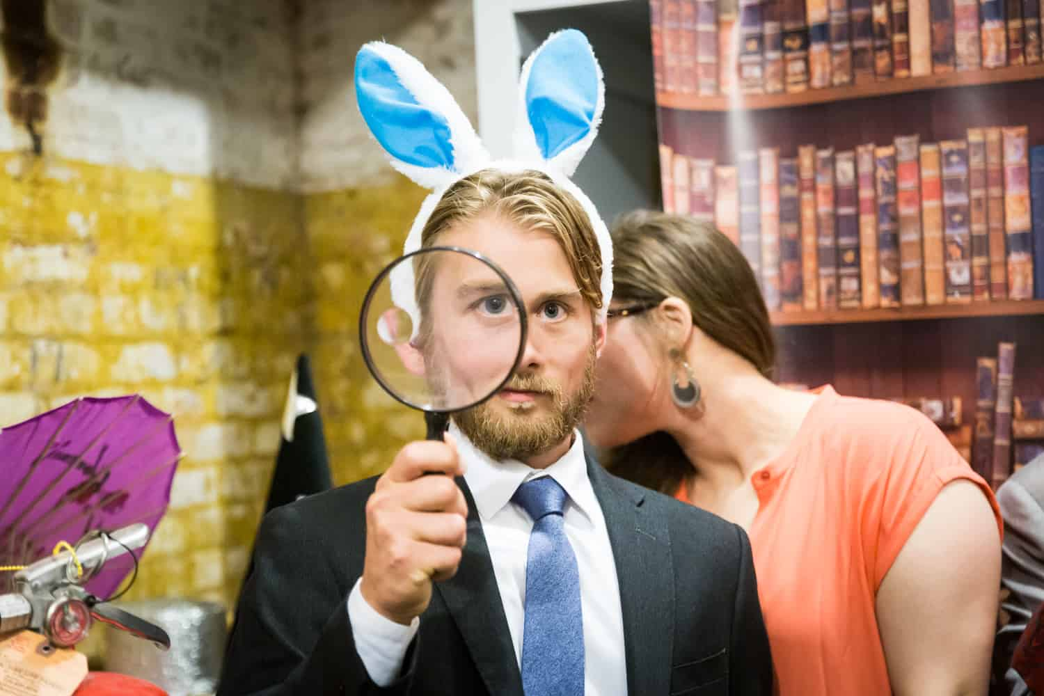 Man wearing bunny ears and holding a magnifying glass in a DIY photobooth