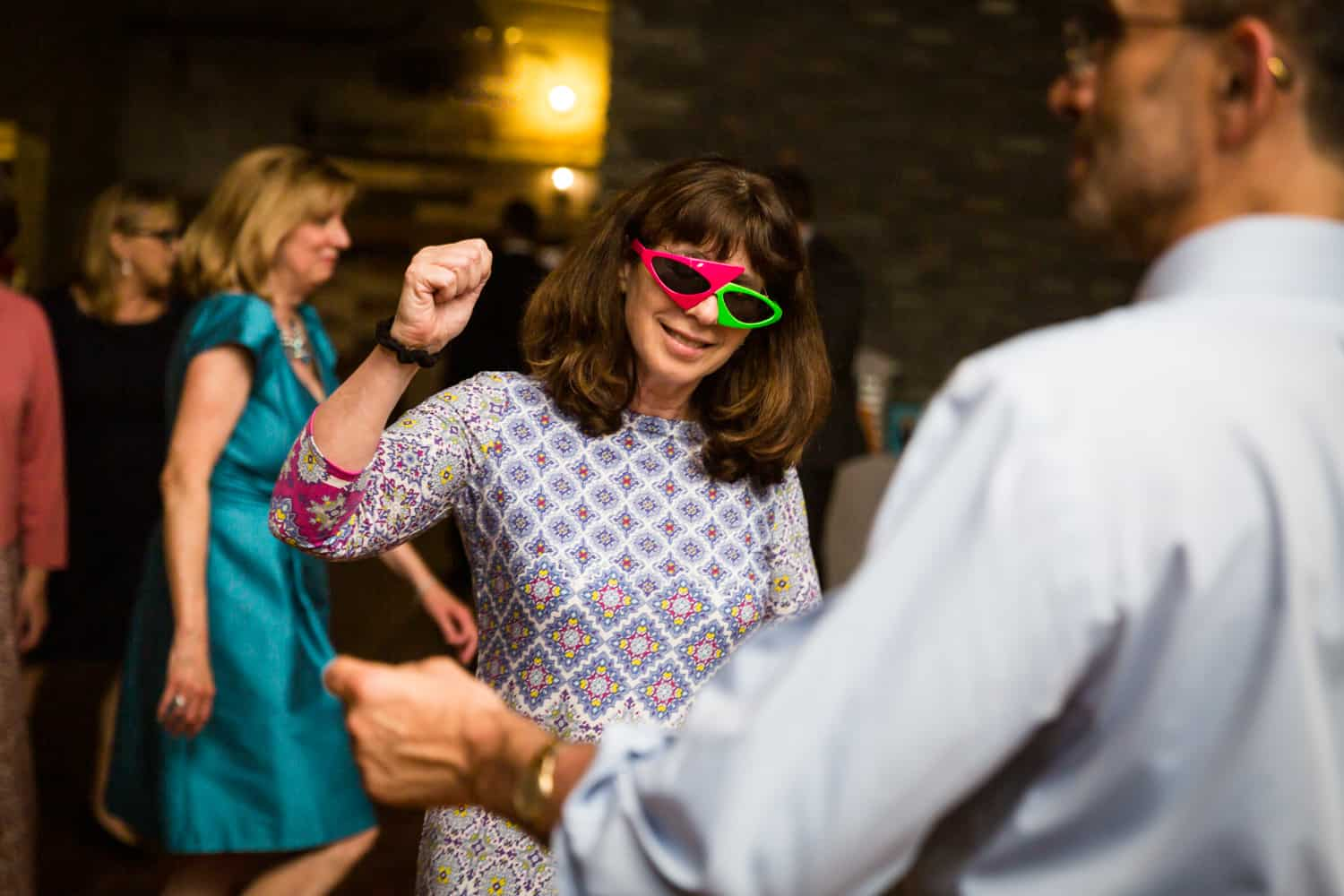 Guest dancing with 80s-style sunglasses at a Greenpoint Loft wedding