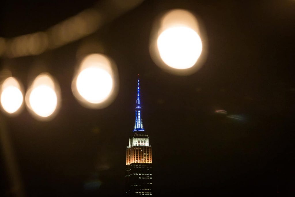 View through light string of Empire State Building at night