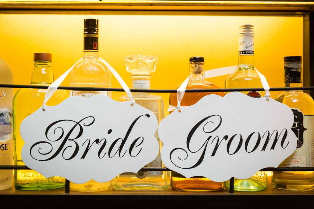 Bride and groom signs at a rehearsal dinner for an article on details your wedding photographer needs to know