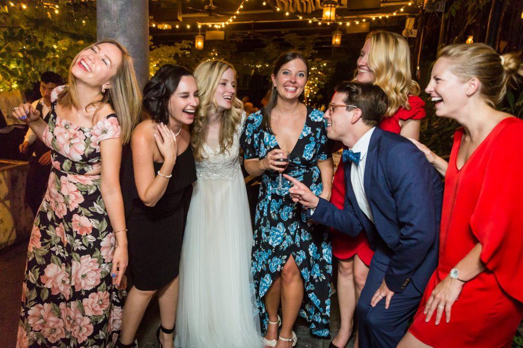 Bride laughing with five female guests and one male guest