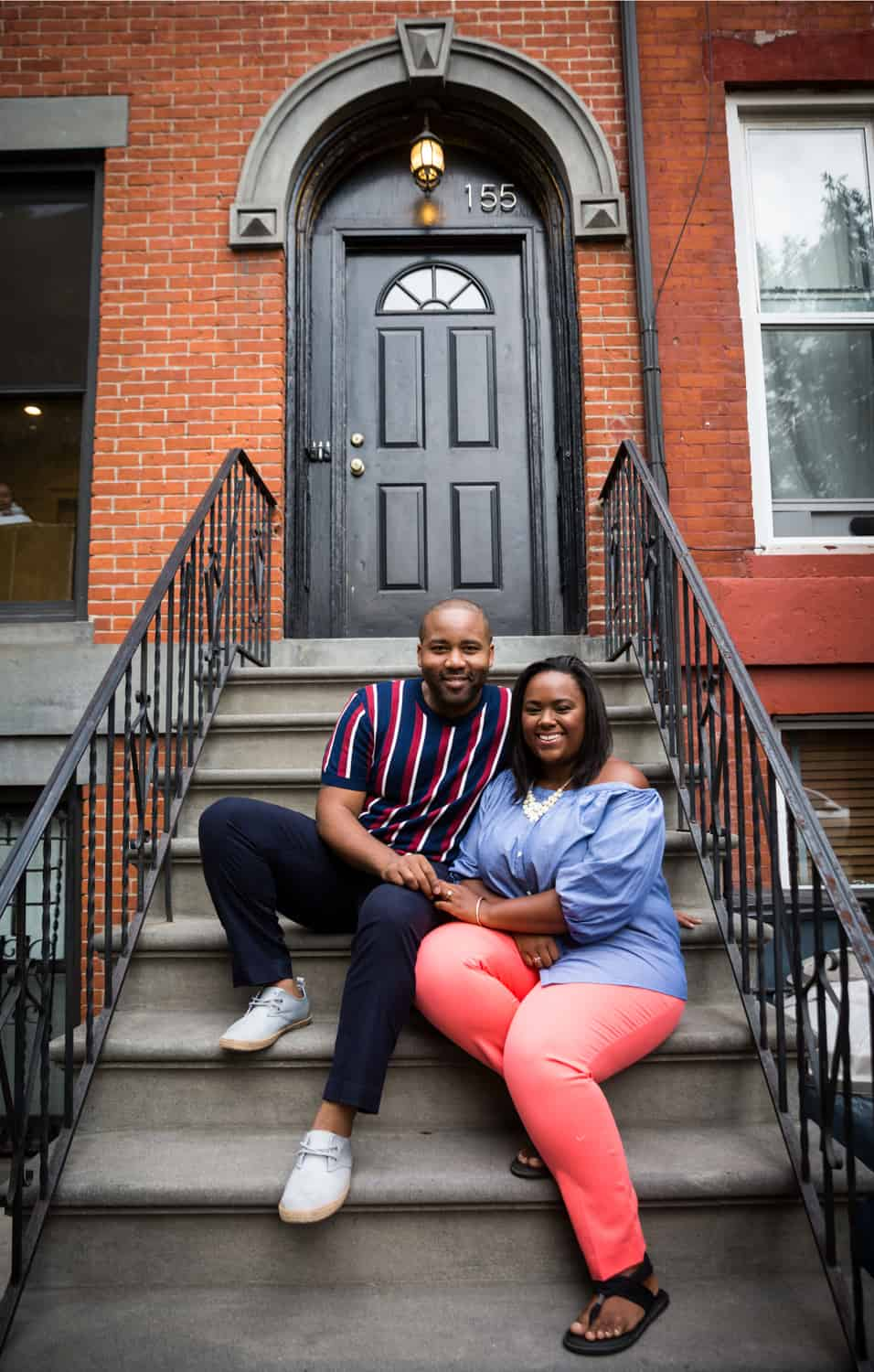 African American couple sitting on stairs in front of Brooklyn brownstone