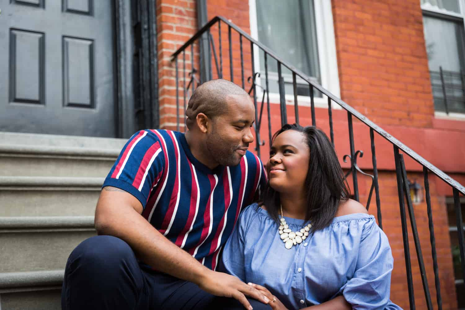 African American couple sitting on stairs in front of apartment building for an article on creative engagement photo shoot ideas