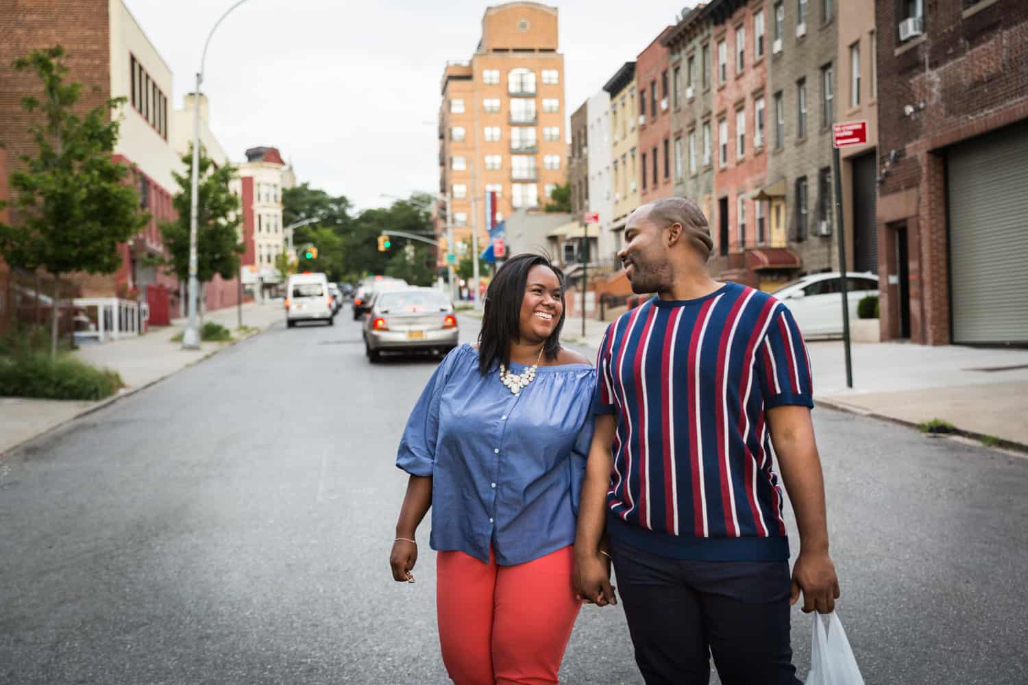 African American couple walking together down Brooklyn street for an article on creative engagement photo shoot ideas