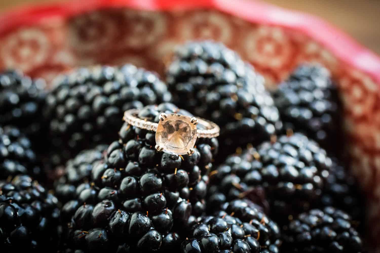 Engagement ring on bowl of blackberries