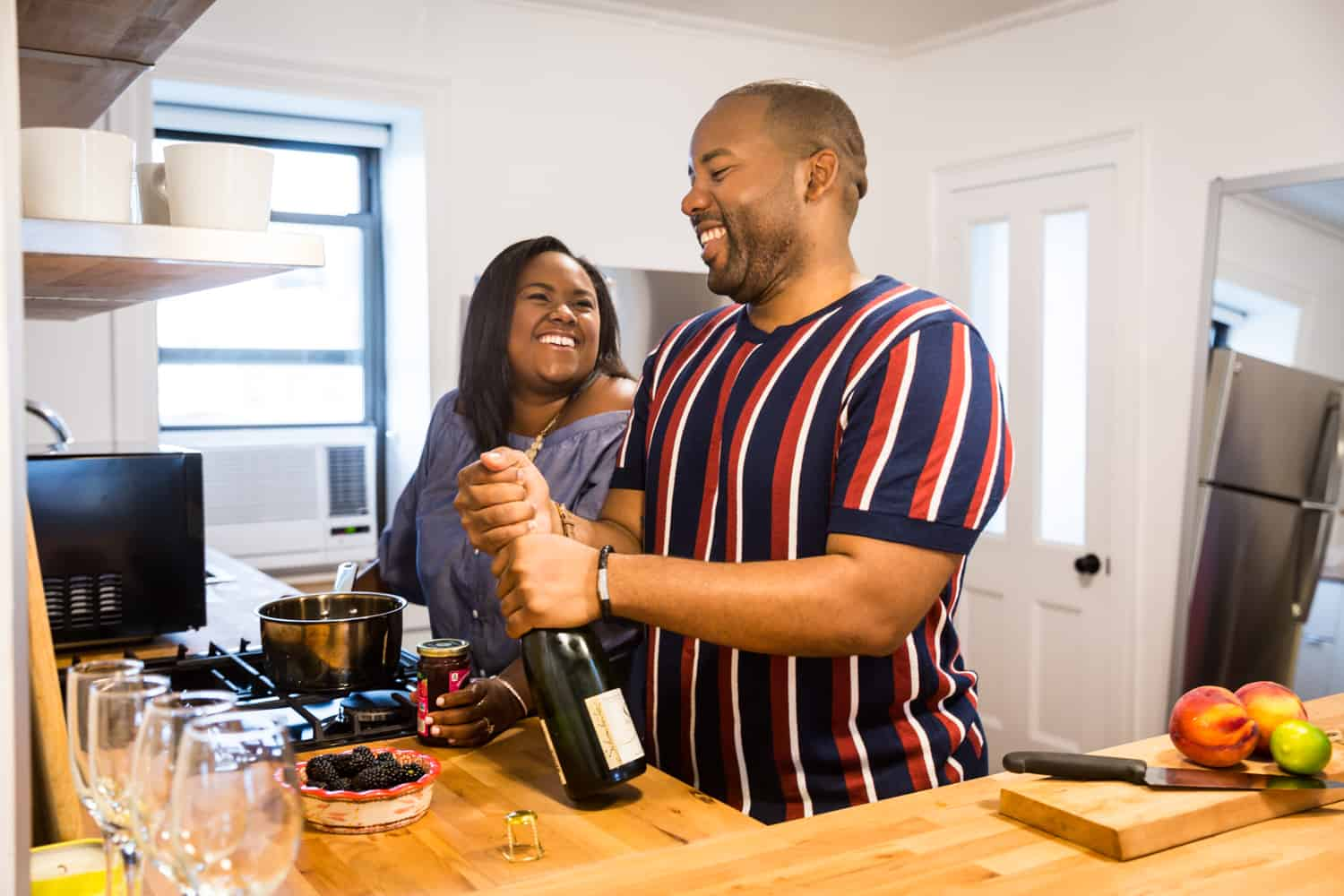 Man opening bottle of champagne in kitchen with woman for an article on creative engagement photo shoot ideas