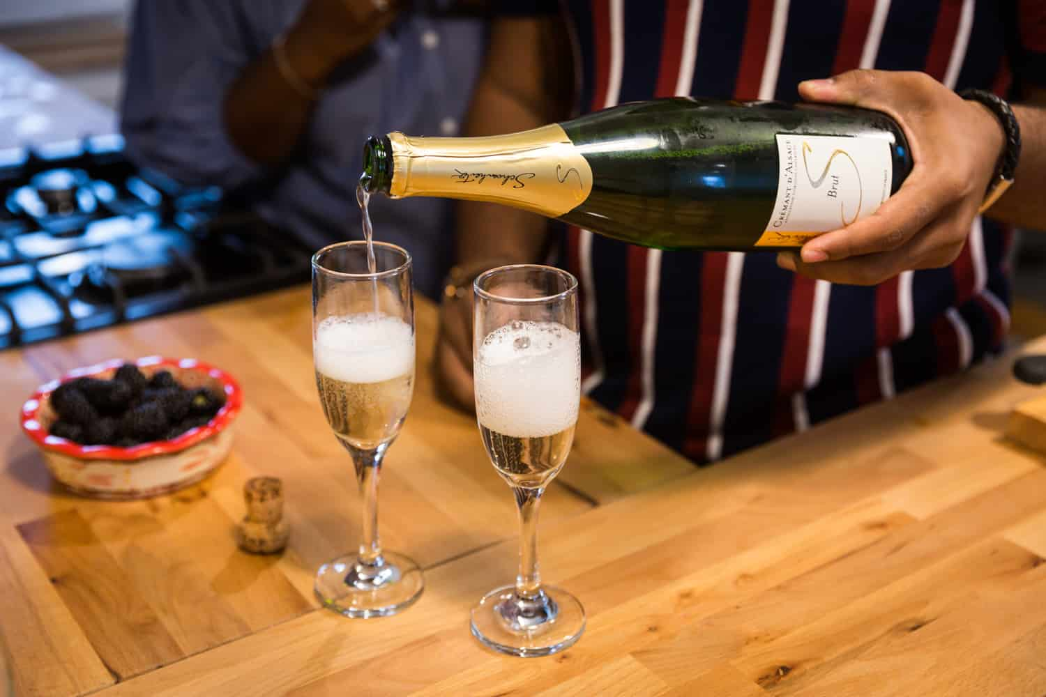 Bottle of champagne being poured into fluted glass on wooden counter