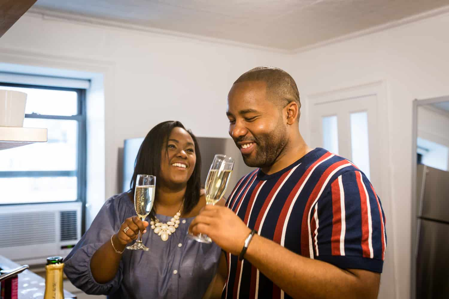 African American couple drinking from champagne flutes for an article on creative engagement photo shoot ideas