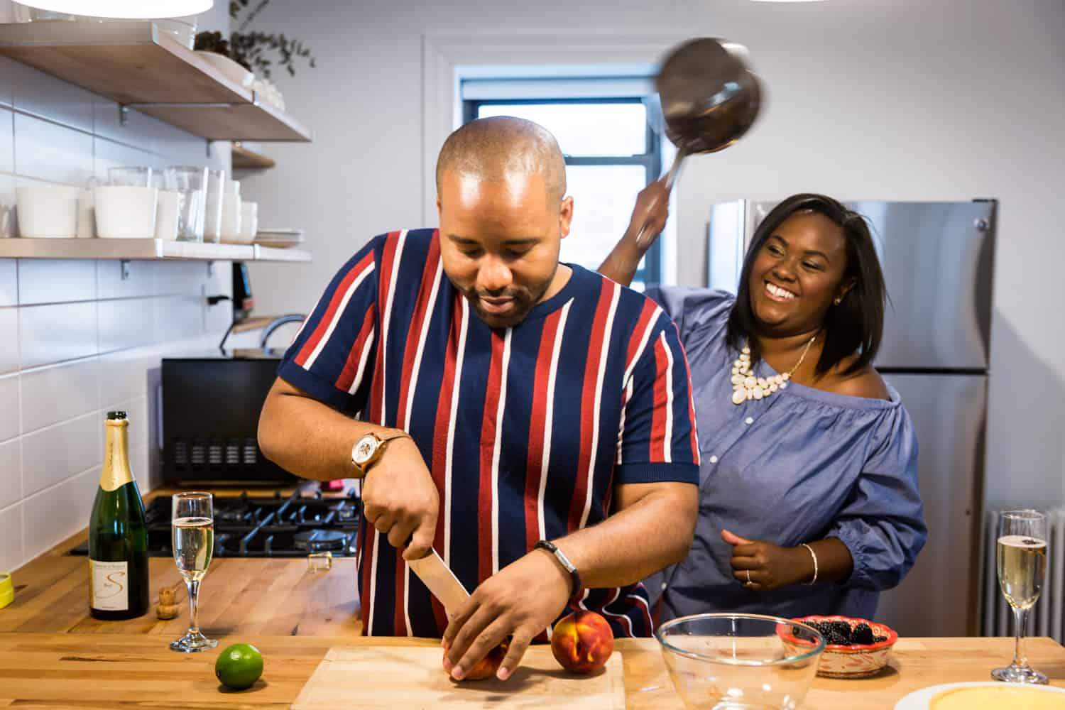 Woman raising pan over man cutting fruit for an article on creative engagement photo shoot ideas