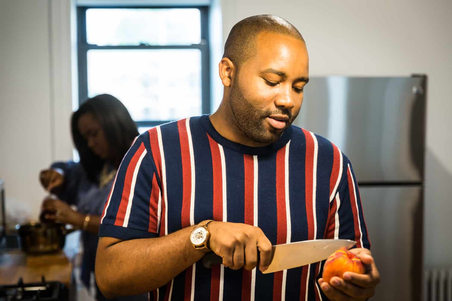 African American man cutting peach for an article on creative engagement photo shoot ideas