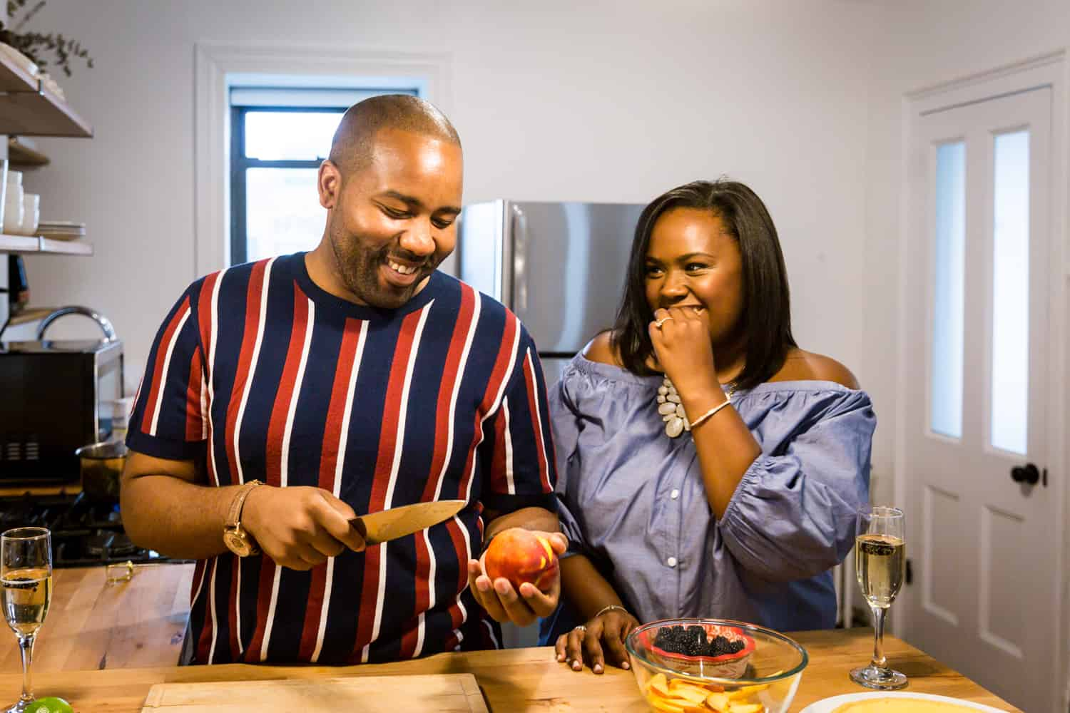 African American couple cooking together for an article on creative engagement photo shoot ideas