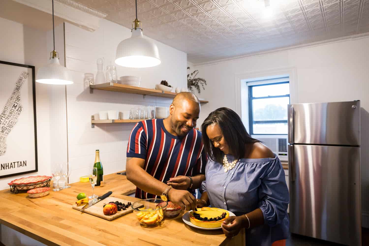 Couple cutting fruit tart for an article on creative engagement photo shoot ideas