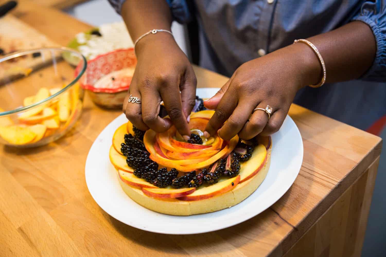 African American woman's hands arranging fruit tart