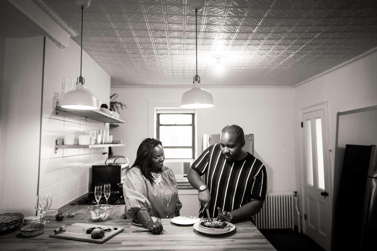Black and white photo of couple cutting fruit tart for an article on creative engagement photo shoot ideas