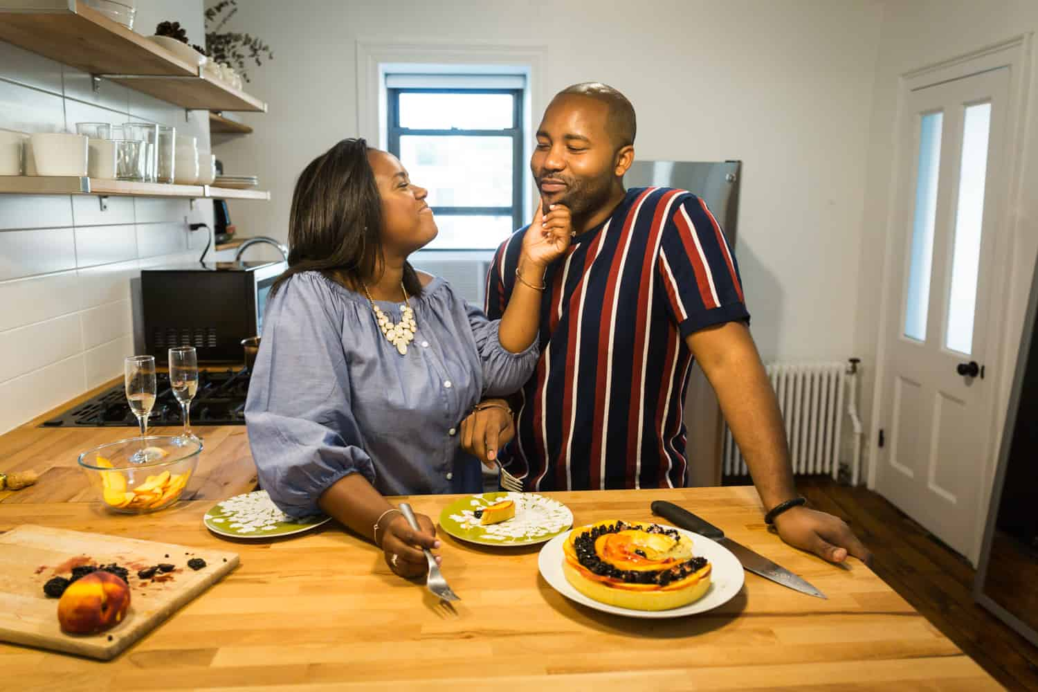 Woman touching man's face in kitchen for an article on creative engagement photo shoot ideas