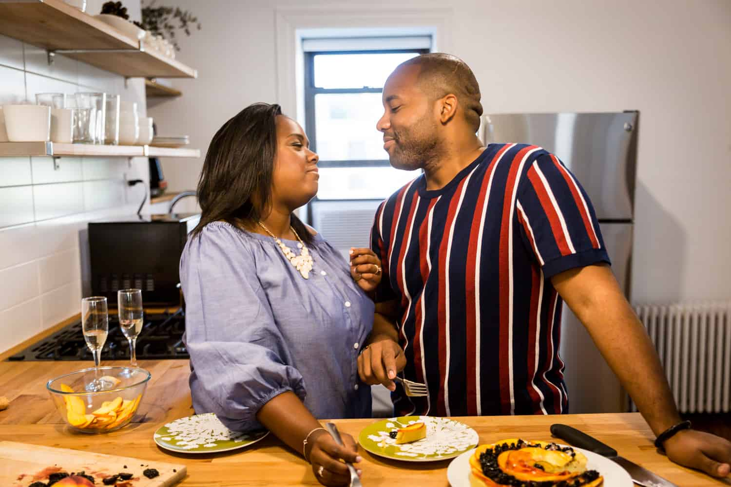 African American couple eating fruit tart in kitchen for an article on creative engagement photo shoot ideas