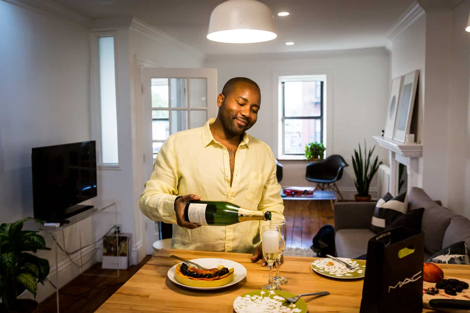 African American man pouring bottle of champagne for an article on creative engagement photo shoot ideas