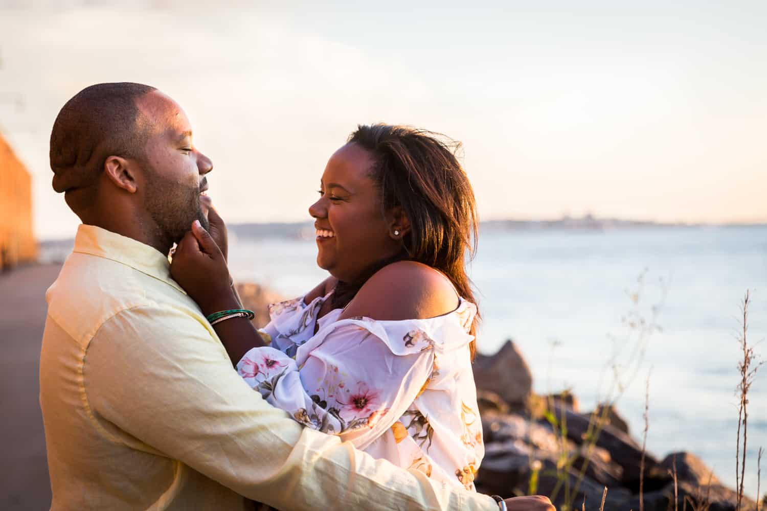 African American couple hugging in front of NYC waterfront for an article on creative engagement photo shoot ideas