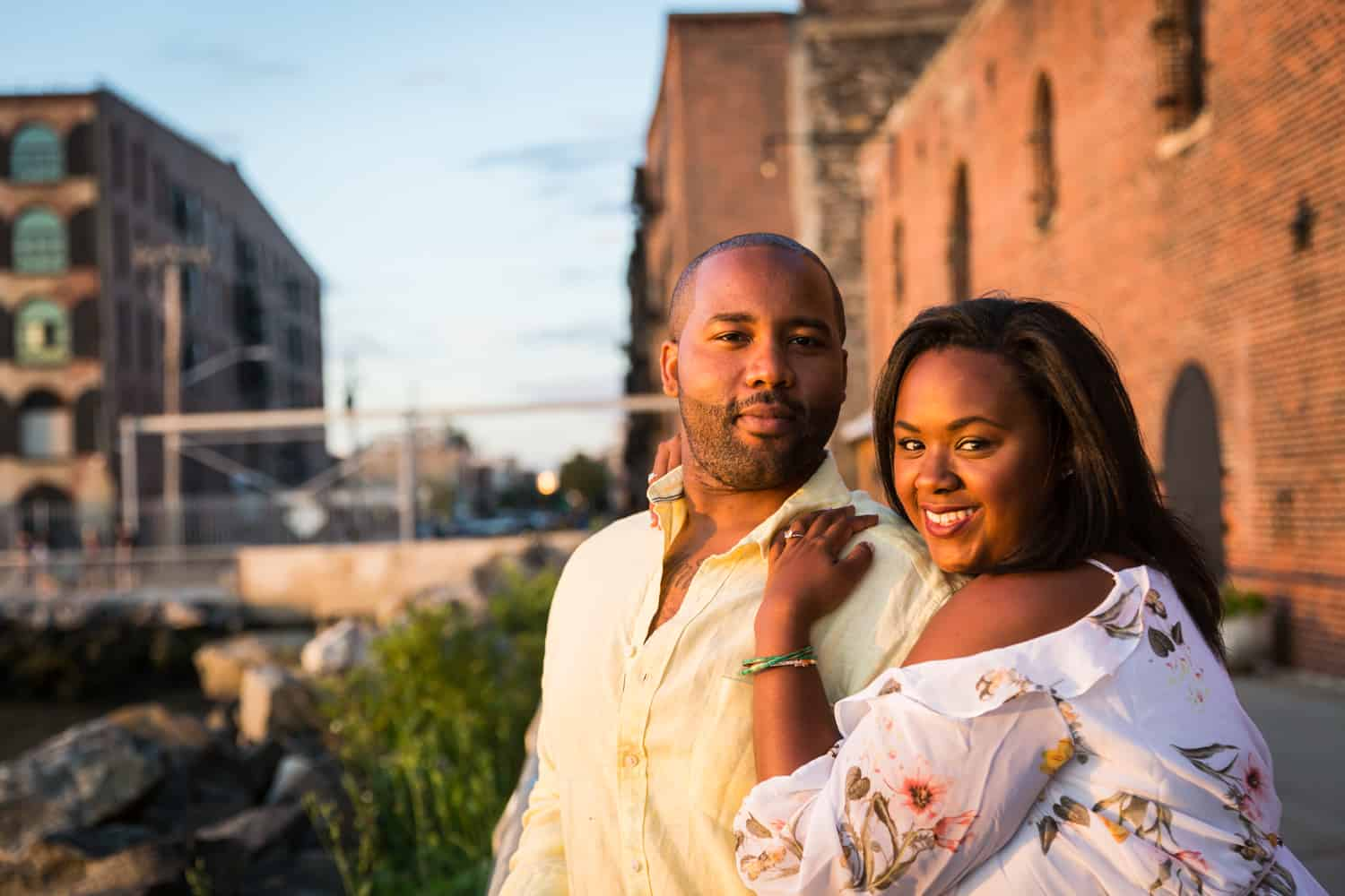 Couple in front of brick building in Red Hook for an article on creative engagement photo shoot ideas