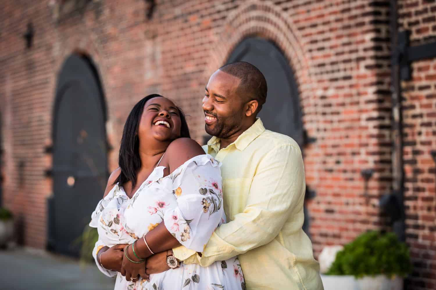 African American couple laughing in front of brick building during engagement shoot