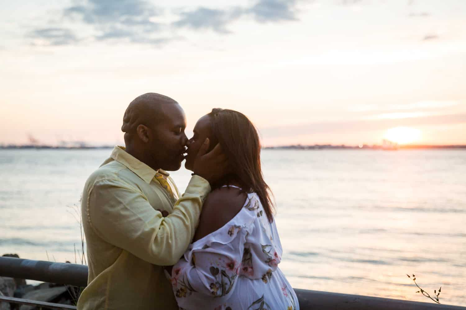 Couple about to kiss in front of NYC waterfront for an article on creative engagement photo shoot ideas