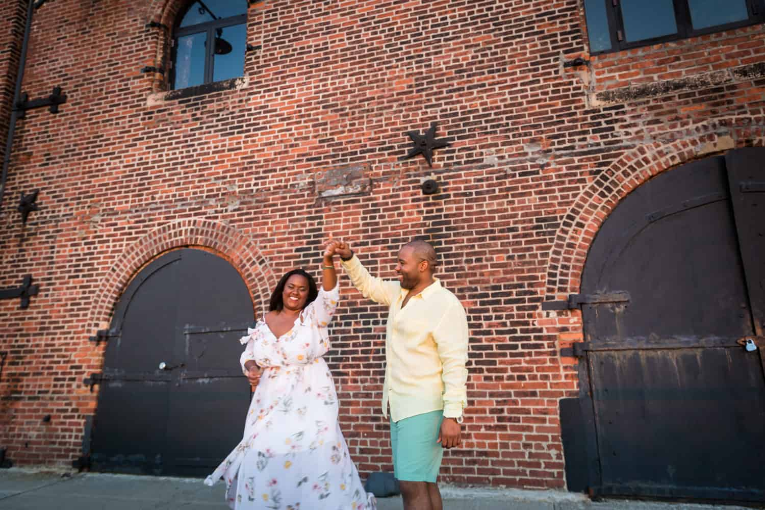 African American couple dancing in front of brick building in Red Hook