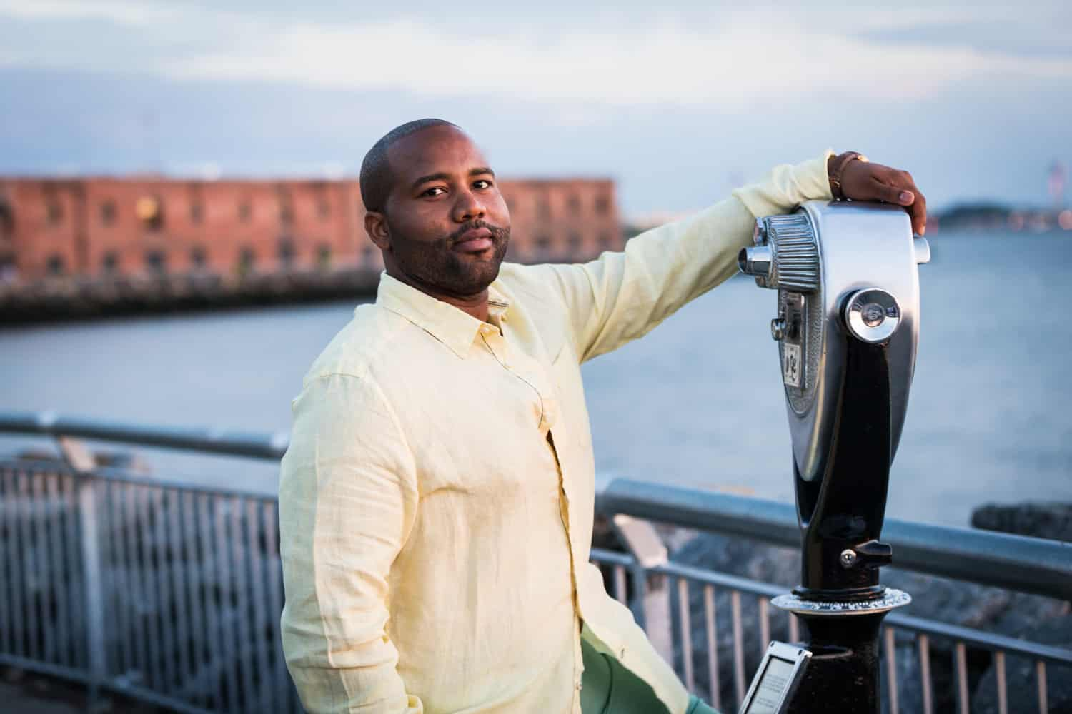 African American man standing in front of Red Hook waterfront with hand on view master