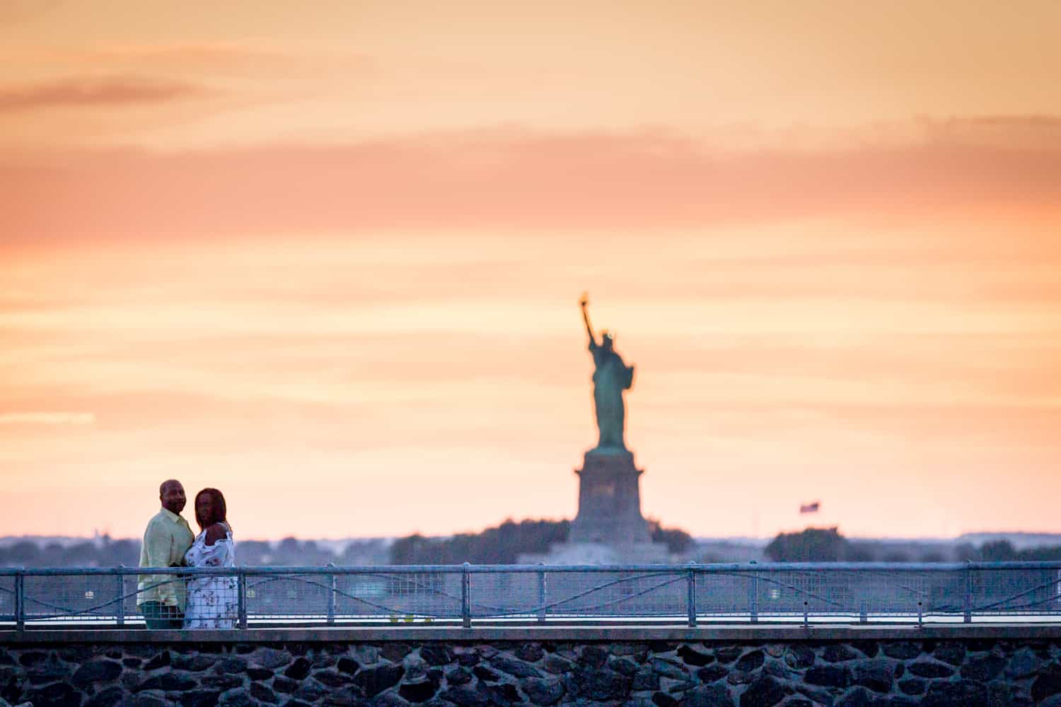 Couple on dock with Statue of Liberty in background at sunset