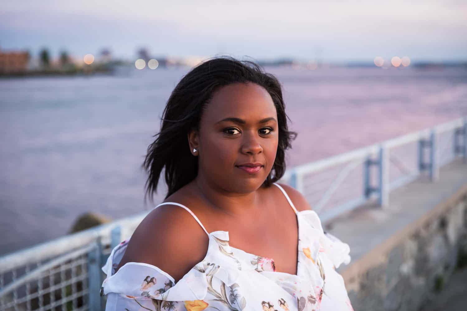 African American woman in white floral dress standing in front of waterfront railing