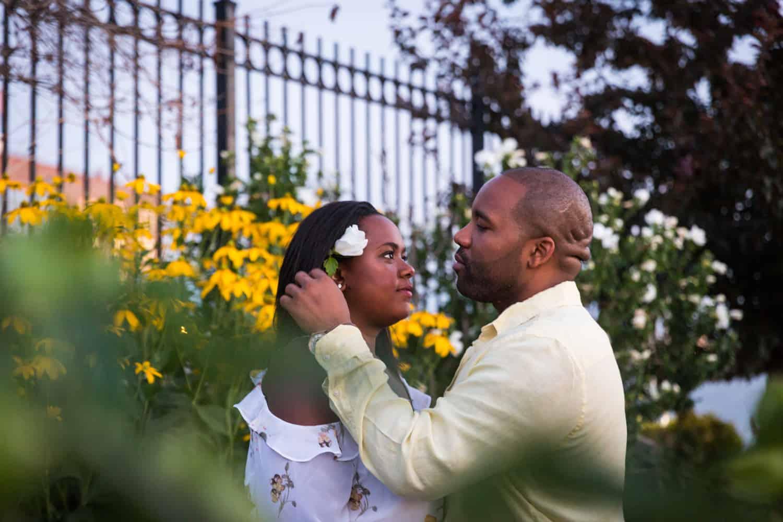 Man putting flower in woman's hair