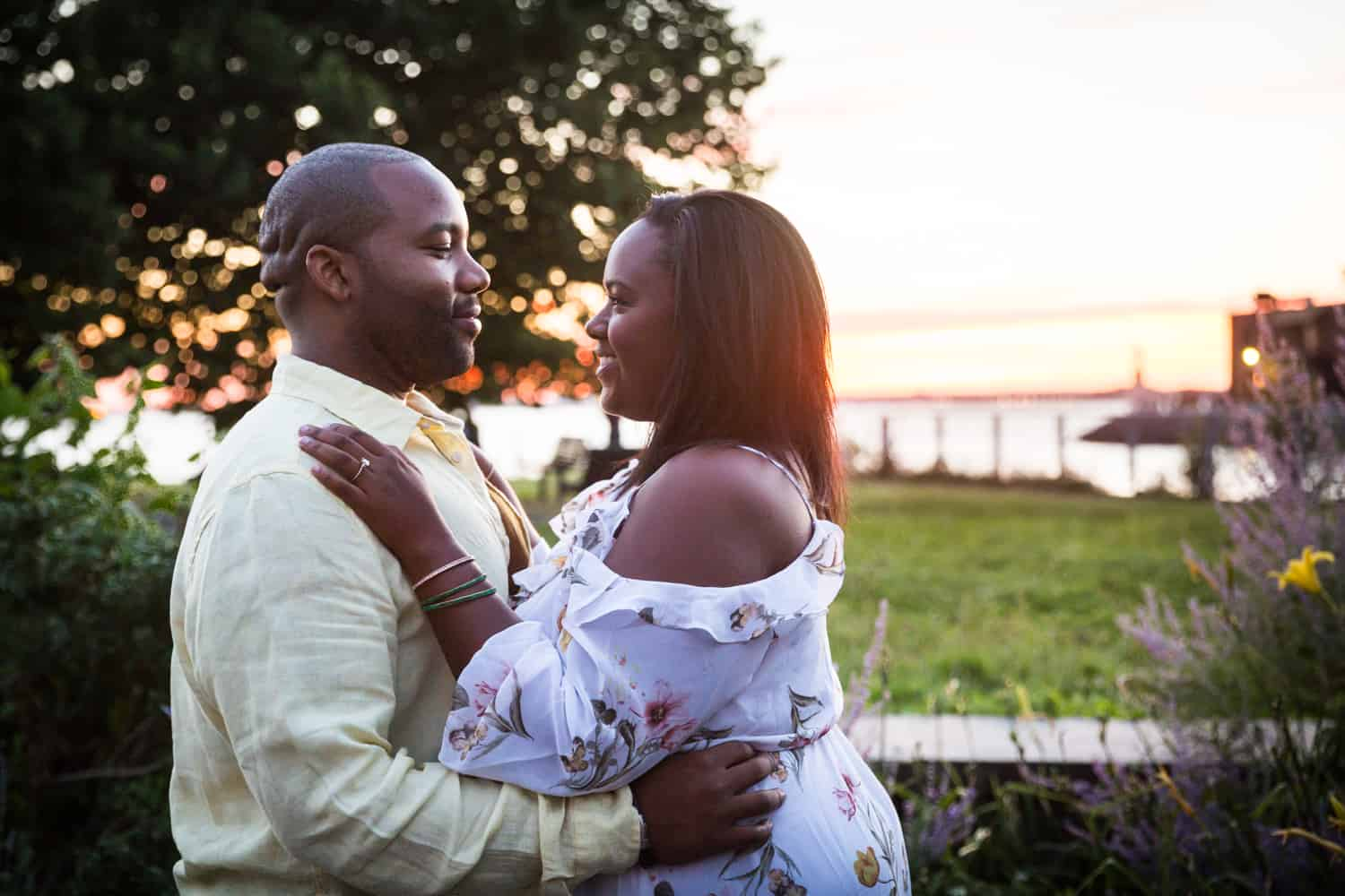 African American couple hugging along Red Hook waterfront during engagement shoot