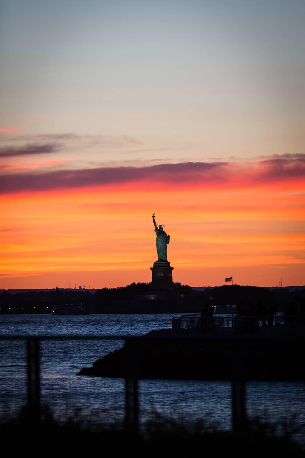 Red Hook waterfront at sunset with Statue of Liberty in background