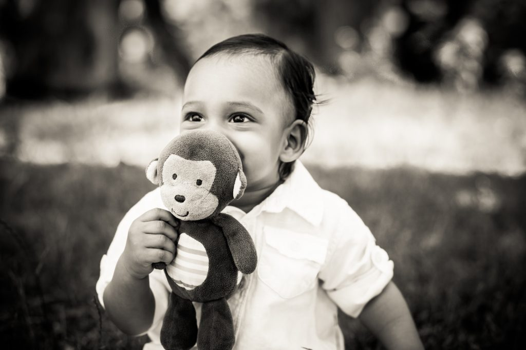 Black and white photo of baby chewing on stuffed toy monkey