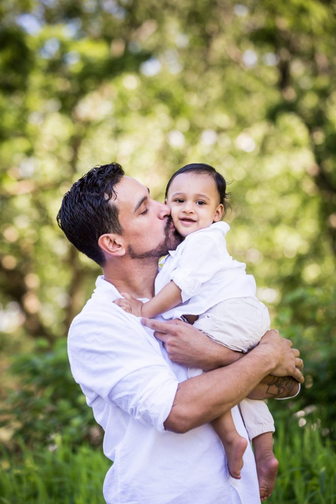 Father kissing little son on cheek in Forest Park