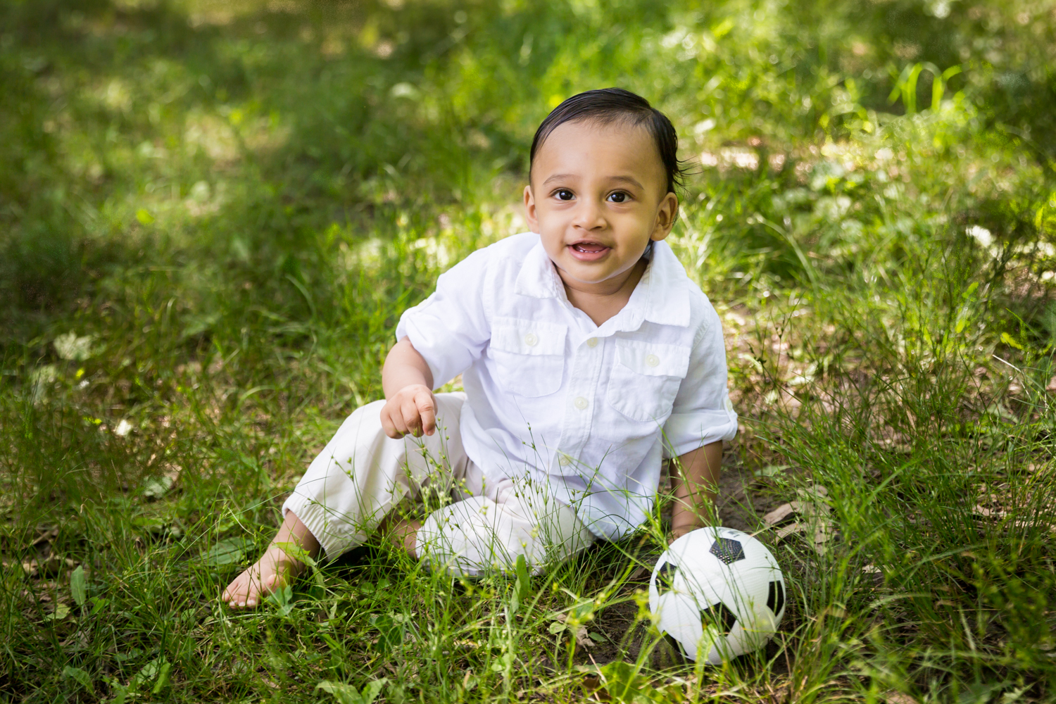 Forest Hills family portrait of toddler sitting in grass with soccer ball
