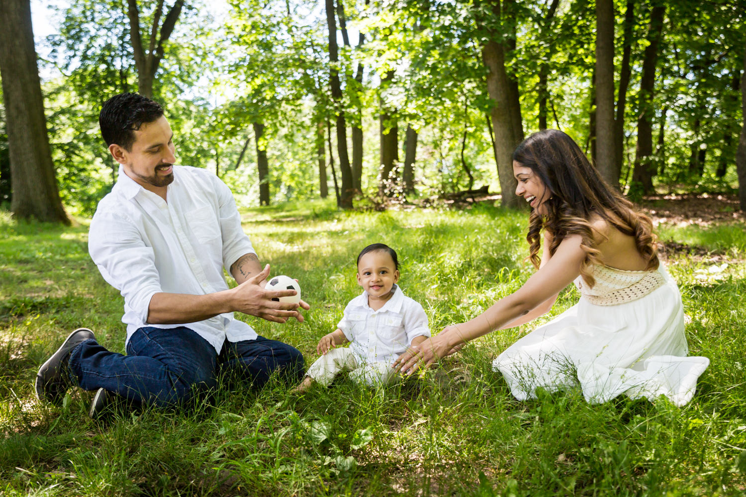 Forest Hills family portrait of parents playing in grass with son