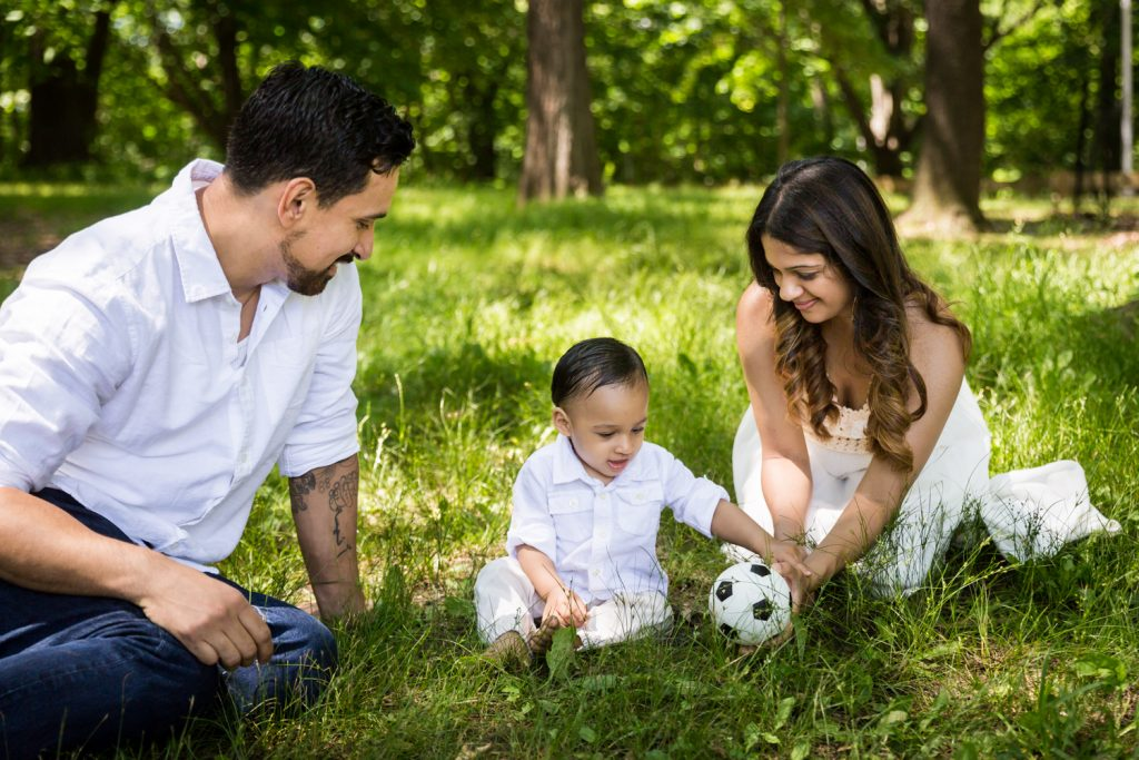 Parents playing in grass with son and soccer ball