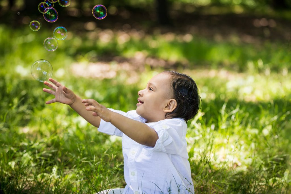 Little boy playing grass with bubbles