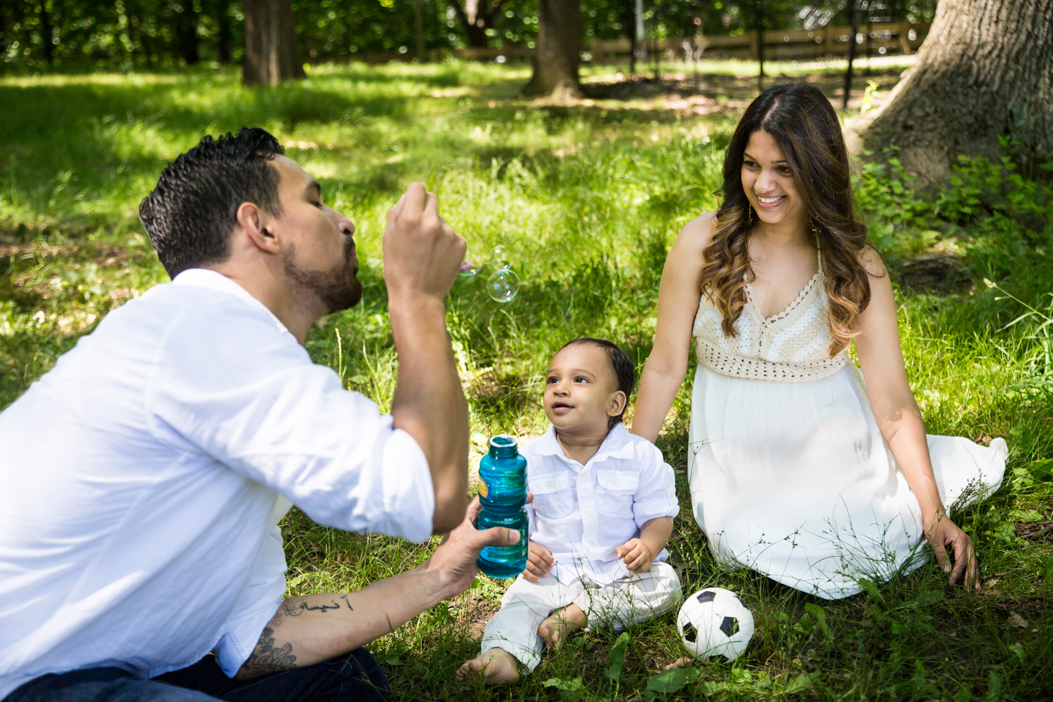 Parents sitting in grass and blowing bubbles with son