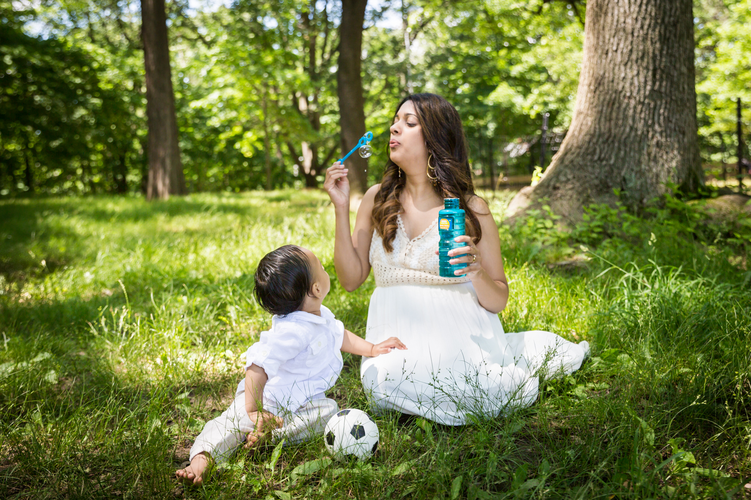 Mother blowing bubbles with son in grass