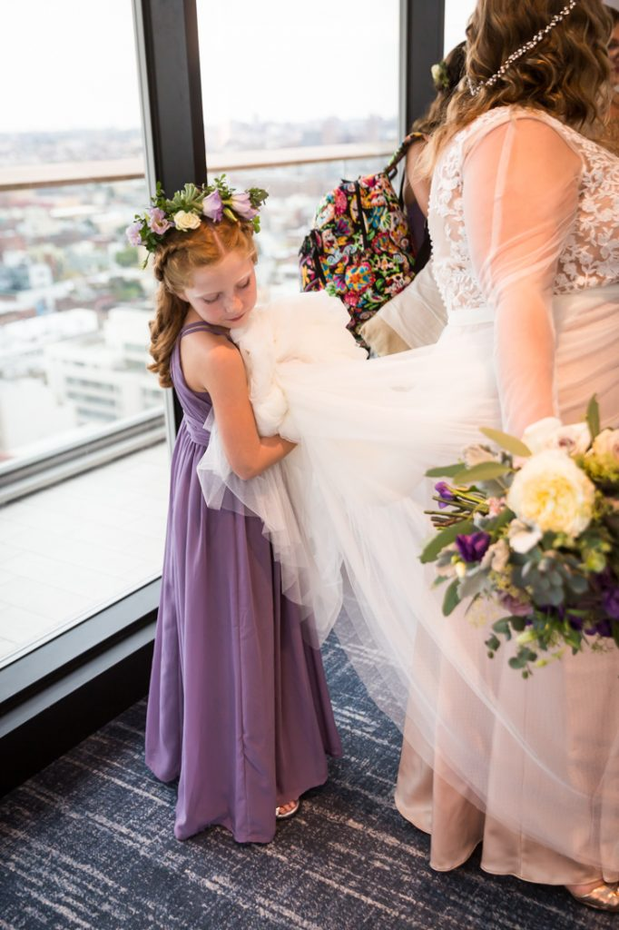 Flower girl holding bride's dress for a 26 Bridge wedding