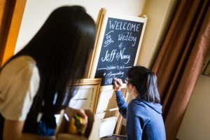 Creating a chalk introduction board at a Bear Mountain Carousel wedding