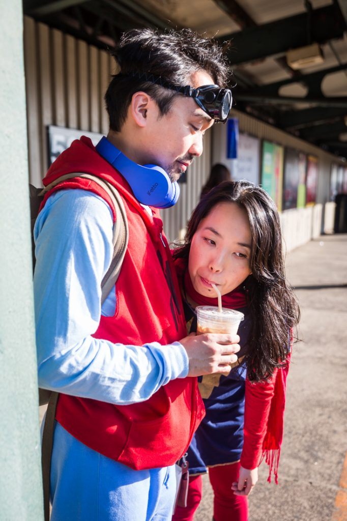 Couple sipping from a cup dressed as Spiderman and Supergirl for a Comic Con engagement shoot