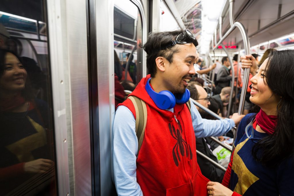 Couple commuting on the subway dressed as Spiderman and Supergirl for a Comic Con engagement shoot
