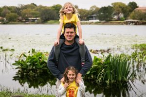 Groom-to-be and kids by a lake