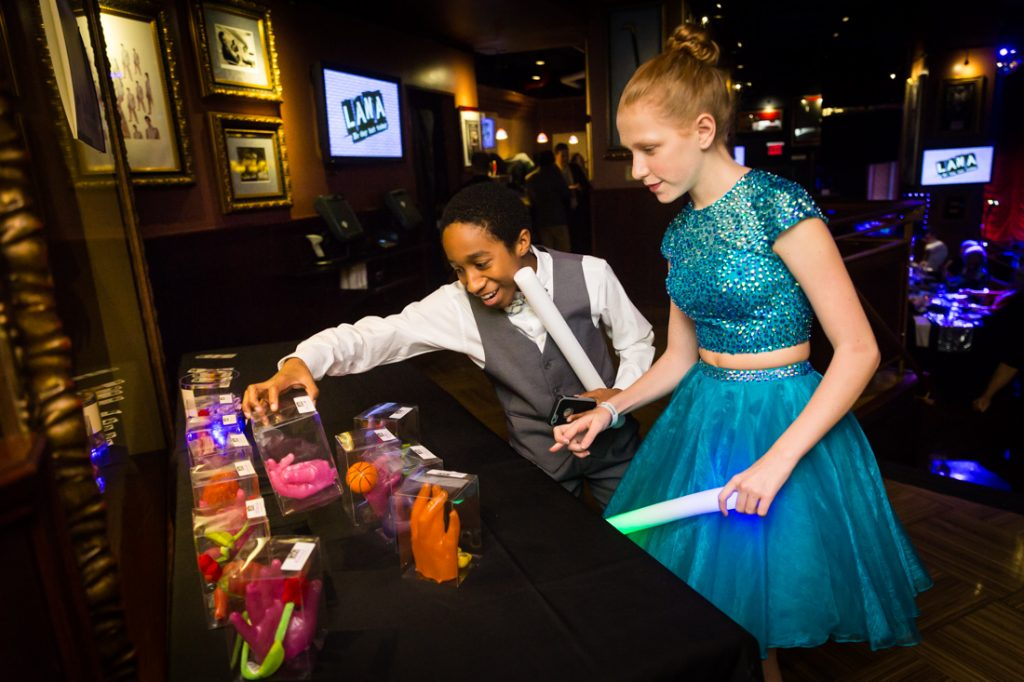 Kids looking at wax hands at a bat mitzvah for an article on 'How to Find a Venue'
